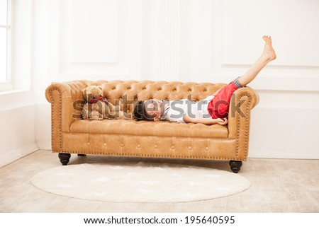 Happy young boy laughing while lying on sofa at home - stock photo