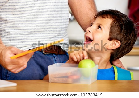 happy young boy looking up at dad with healthy apple in lunch box for school - stock photo