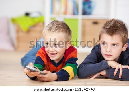 Happy young boy lying on his stomach on the floor with a friend or his brother using a remote control to change the program on the television - stock photo
