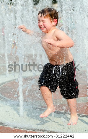 Happy young boy or kid has fun playing in water fountains at Centennial Olympic Park in Atlanta, Georgia, on hot day during summer. - stock photo