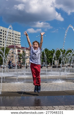 Happy young boy or kid has fun playing in water fountains, on hot day during summer. - stock photo