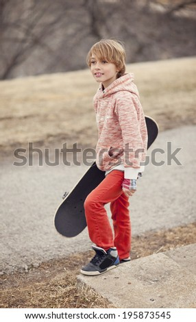 Happy young boy outside having fun with his long board - stock photo