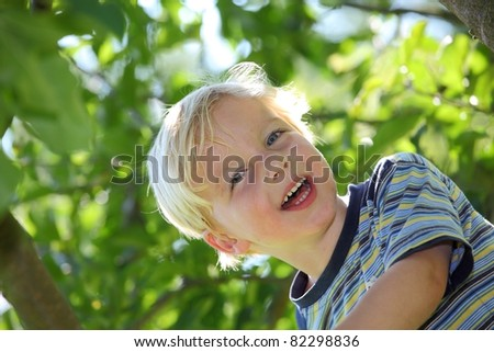 Happy young boy outside in the garden - stock photo