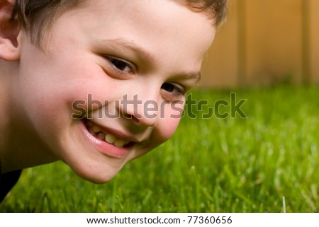 happy young boy outside in the grass