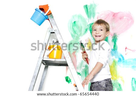 happy young boy painting over white