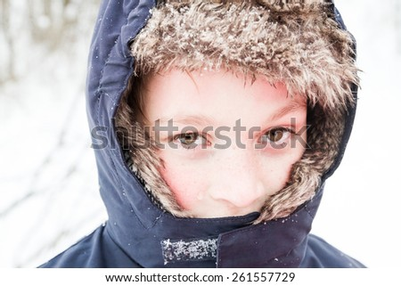Happy young boy playing in the snow - stock photo