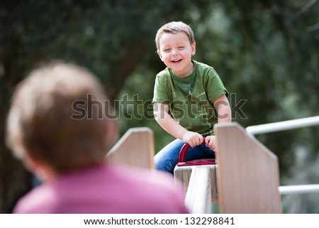 Happy young boy playing on a playground teeter totter - stock photo