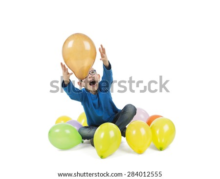 Happy young boy playing with balloons against a white background - stock photo