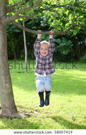 Happy young boy plays in the garden - stock photo