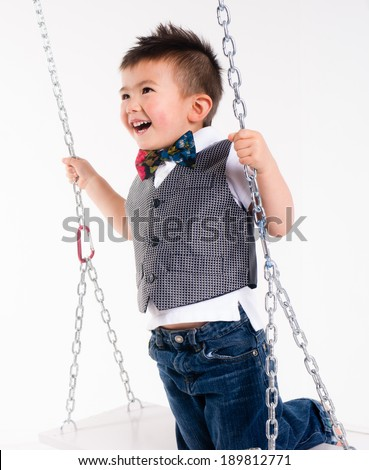 Happy Young Boy Plays Swing Suspended Moving Laughing Child Playtime - stock photo