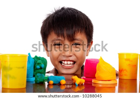 happy young boy put his chin on top of the table - stock photo