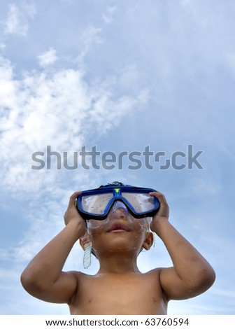 happy young boy ready to swim while wearing blue goggle - stock photo