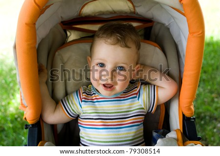 Happy young boy sitting in the baby carriage - stock photo