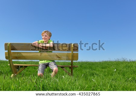 Happy young boy sitting on a bench in summer - stock photo