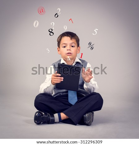 Happy young boy sitting on the floor with legs crossed and using a tablet. - stock photo
