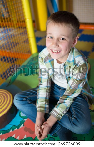 Happy young boy smiling in the children's playroom. Close portrait