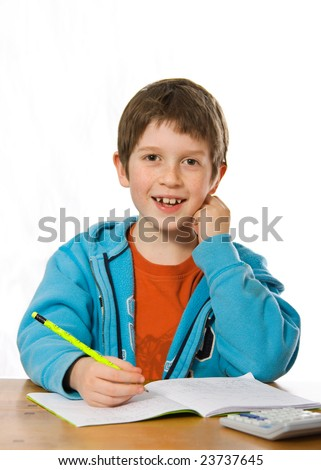 Happy young boy smiling whilst doing homework - stock photo