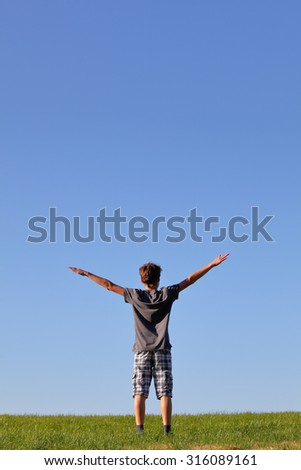 Happy young boy standing in a meadow with blue sky - stock photo