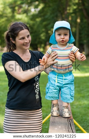 Happy young boy walking with his mother on the bench in the park - stock photo