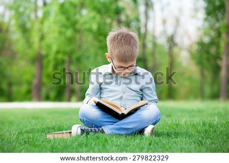 Happy young boy with a books on green grass in the park