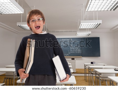 Happy young boy with books in a classroom - stock photo