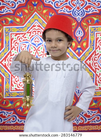 Happy Young Boy with Fez and Lantern Celebrating Ramadan over Ramadan Fabric - stock photo
