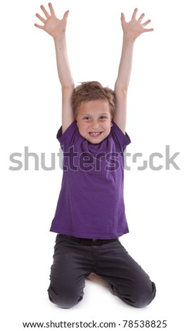 happy young boy with hands raised against white background - stock photo