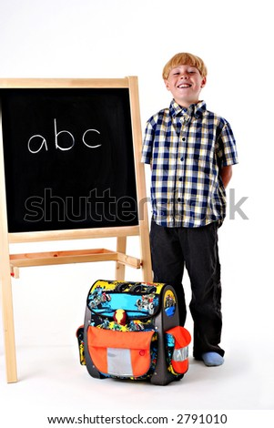 Happy young boy with his school bag next to a black board. - stock photo