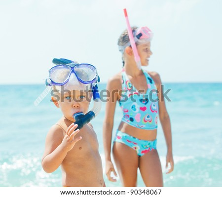 Happy young boy with snorkeling equipment on sandy tropical beach, his sister background. - stock photo