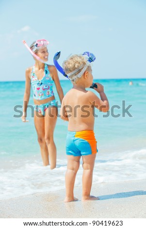 Happy young boy with snorkeling equipment on sandy tropical beach, his sister background. Vertical view - stock photo