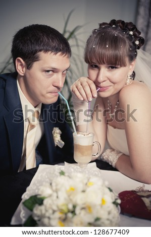 Happy young bride and groom drink a cup of Coffee latte with heart design on their wedding day. Wedding couple - new family! wedding dress. Bridal wedding bouquet of flowers