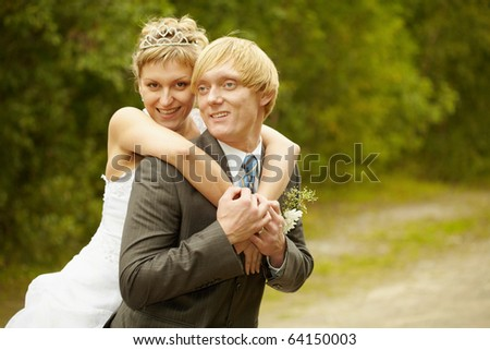 Happy young bride and groom hugging outdoors - stock photo