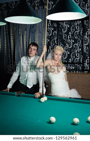 Happy young bride and groom playing billiard at night on their wedding day. Young newlyweds playing billiards at their mansion. Wedding couple. wedding dress. - stock photo
