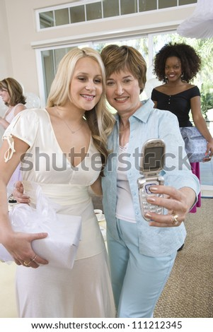 Happy young bride and mother taking self portrait through mobile phone with friends in the background - stock photo