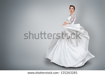 Happy young bride in beautiful long wedding dress - stock photo