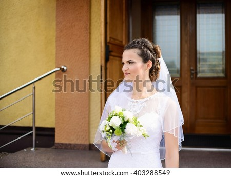 Happy young Bride standing in front of the church holding a bridal bouquet after the wedding ceremony. Sunny Wedding Day.