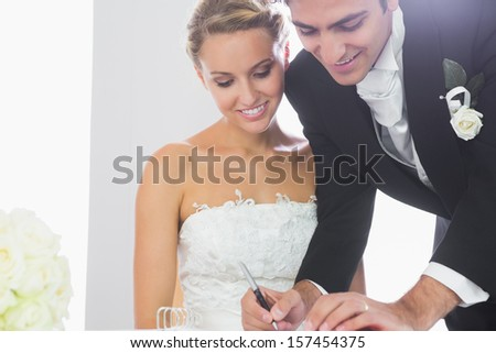 Happy young bridegroom signing wedding contract standing next to his wife - stock photo