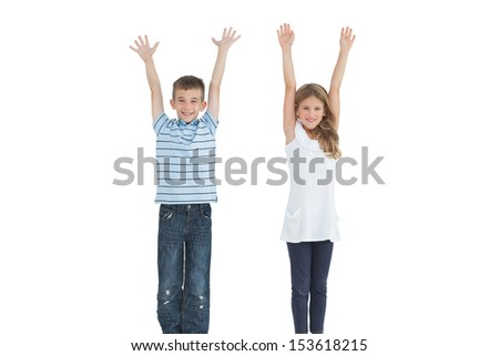 Happy young brother and sister cheering on white background