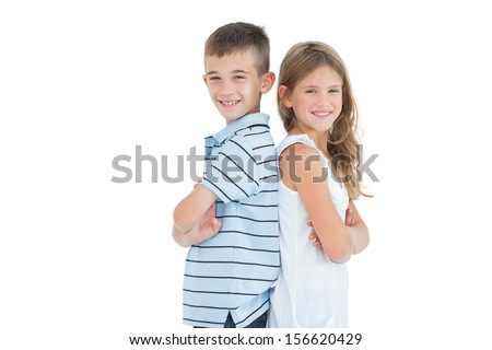 Happy young brother and sister posing back to back on white background - stock photo