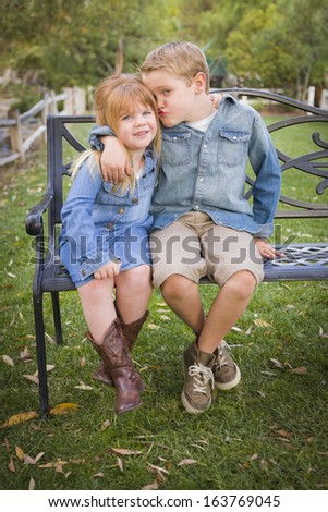 Happy Young Brother and Sister Sitting Together on a Bench Outside. - stock photo