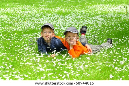 happy young brothers relaxing on a meadow - stock photo