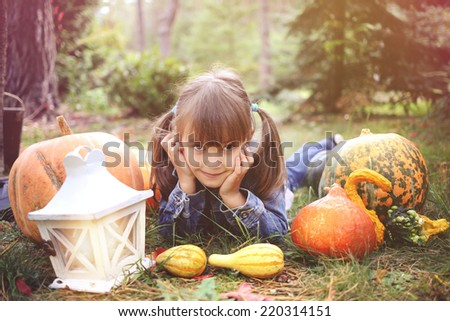 happy young brunette girl lying on the ground with pumpkins
