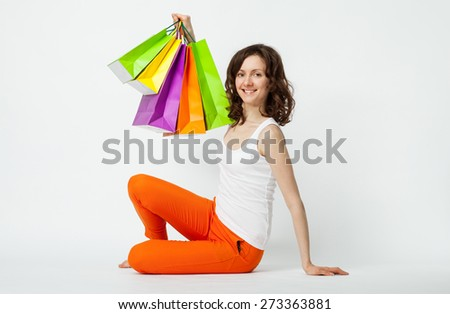 Happy young brunette in orange pants sitting on the floor with shopping bags, studio shot - stock photo