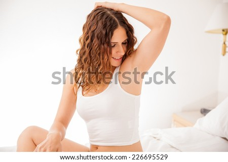 Happy young brunette showing off her recently depilated and smooth armpits - stock photo