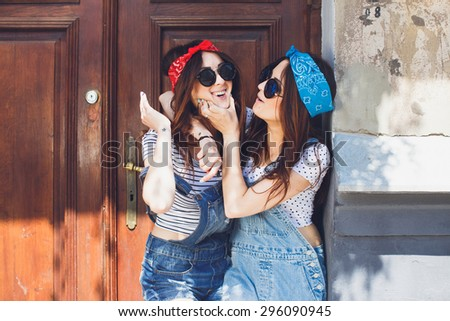 Happy young brunette twins sisters, in stylish sunglasses, hugging and laughing. Having fun time together. Wearing denim overalls bright bandanas, posing in front of old doors. Outdoors. Copy space. - stock photo