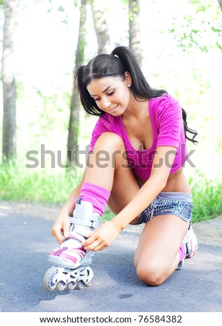 happy young brunette woman fastening the roller skates and is getting ready to ride  in the park - stock photo