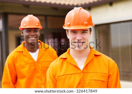 happy young builder and co-worker in front of new house - stock photo