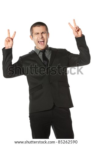 Happy young business man celebrating success shouting and showing victory signs over white background