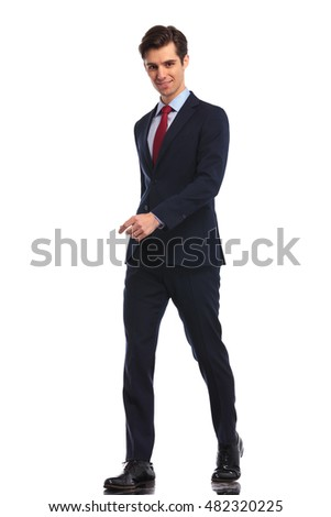 happy young business man in suit and tie walking on white background in studio