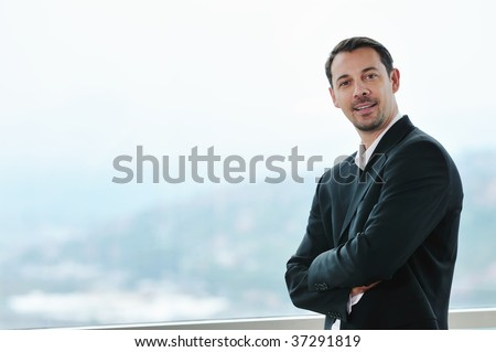 happy young business man portrait in suit  with isolated blurred background - stock photo
